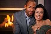 Portrait of beautiful young interracial couple, smiling at home by fireplace.