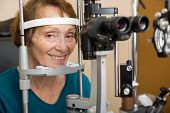 image of slit  - Smiling senior woman undergoing eye examination test with slit lamp in store - JPG
