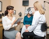 Female ophthalmologists examining senior woman with phoropter in store