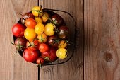 Baby Heirloom Tomatoes in a bucket on a rustic wooden table top. Horizontal format, looking down on