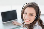 Close up portrait of a smiling businesswoman wearing headset in front of laptop in office