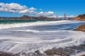White waves on Baker Beach as Golden Gate Bridge on background under blue sky with white clouds in San Francisco, USA.