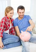 money, home, finance and relationships concept - smiling couple with piggybank sitting on sofa