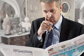 Businessman reading a newspaper while smoking cigars