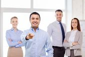 business and office concept - smiling handsome businessman with team in office pointing finger at yo