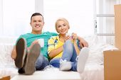 moving, home and couple concept - smiling couple relaxing on sofa with tea cups in new home