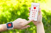 image of watch  - Female hands holding touch phone and smart watch with mobile app health sensor