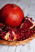 Ripe pomegranate on wicker mat on color wooden background