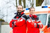 Emergency doctor and nurse standing in front of ambulance car