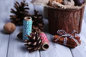 Composition with natural bump, thread, cinnamon sticks on wooden background