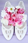 Beautiful wedding bouquet and shoes on wooden background