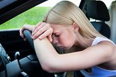 Woman Leaning Head On Steering Wheel