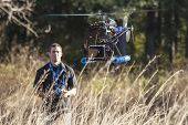 stock photo of helicopters  - man flying uav helicopter with video camera - JPG