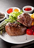 Fresh beef steaks served on plate with grilled vegetable.
