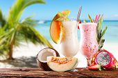 Fresh summer drinks with exotic fruits. Blur beach on background