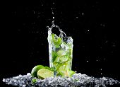 stock photo of mojito  - Studio shot of fresh mojito drink with ice cubes and splash on black background - JPG
