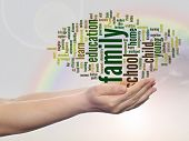 Concept or conceptual family and education abstract word cloud, human man hand, rainbow sky backgrou