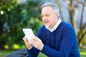 Mature man using a tablet at the park