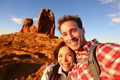 Happy couple taking selfie self-portrait photo hiking. Two friends or lovers on hike smiling at came