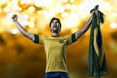 stock photo of patriot  - Brazilian soccer player celebrating on a Yellow lights background - JPG