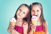 Portrait of 5 years old kid girls eating tasty ice cream over blue