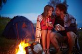 stock photo of fire  - Young couple sitting by the fire and drinking tea outside - JPG
