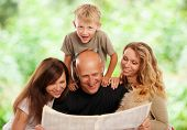 Family reads the newspaper outdoors