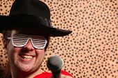 stock photo of crazy hat  - Crazy rock and roller singer with a big black hat party glasses in front of a cheetah skin background - JPG