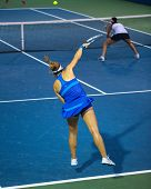 KUALA LUMPUR - APRIL 20, 2014: Timea Babos of Hungary (blue) serves during the doubles final of the