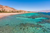 Aquamarine water and underwater corals along empty beach on popular resort of Eilat on Red Sea in Is