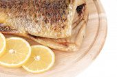Fried carp on wooden platter with lemon.