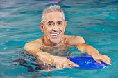 Happy senior man with kickboard in water of swimming pool