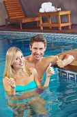 Happy smiling couple in swimming pool holding their thumbs up