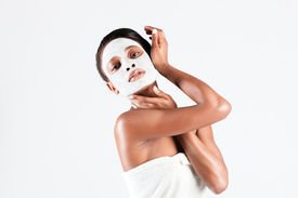 stock photo of mud pack  - Young African woman in Studio doing body care with refreshing facial mask for young and beautiful skin and relaxation - JPG