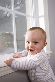 picture of stand up  - Happy six month old baby pulling himself up on window sill - JPG