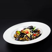 Italian Pasta With Mussels Marinara, Cherry Tomatoes And Herbs For A Tasty Seafood Meal Over Black T
