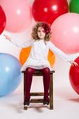Girl Sitting On A Chair On A Background Of Big Colorful Balloons
