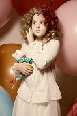 Surprised Girl With A Soft Toy Surrounded By Huge Balloons