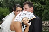 Young bride and groom couple posing with a white fan