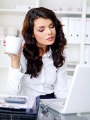 Young businesswoman with long wavy brown hair working on her laptop and drinking a mug of coffee as she sits at her desk in the office