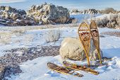 vintage Huron and Bear Paw snowshoes in winter scenery on a parking lot or trailhead
