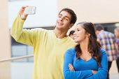 friendship, education and people concept - group of smiling students making selfie with smartphone o