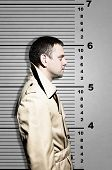 Killer Standing On Height Ruler For Photo In Prison