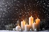 Burning candles and fir branch on snow