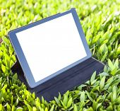 Digital tablet computer with isolated screen over bright green grass background