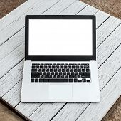 Open laptop with isolated screen on white wooden desk.