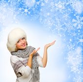 Young girl shows welcome gesture on blue winter background