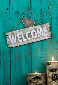 Welcome sign with heart and burning candles hanging on antique teal blue weathered background