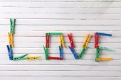 Love word formed with colorful clothespins on wooden background