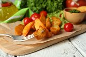 Homemade fried potato on wooden cutting board on wooden background